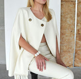 The Casimir cape is a stunning white cape in a luxurious wool. The asymmetrical fringe on the front adds a touch of drama. A two button snap closure in the front.