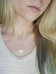 Silver sun necklace on model