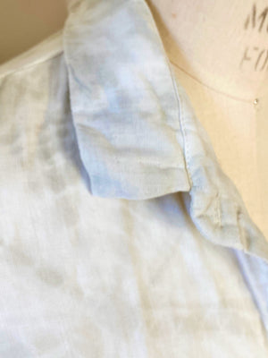 This is a close up photo of the collar and shoulder of a organic cotton Smock Top for women by Modern Shibori. It's hand dyed with botanical dyes using rosemary and  sustainable shibori techniques.