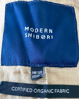This is a photo of the main label and certified organic fabric labelof an organic cotton Smock Top for women by Modern Shibori. It's hand dyed with botanical dyes using walnuts