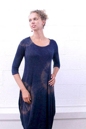 This is a photo of a model wearing the pink blue eclipse knit shibori dress. It's hand dyed using madder root and indigo