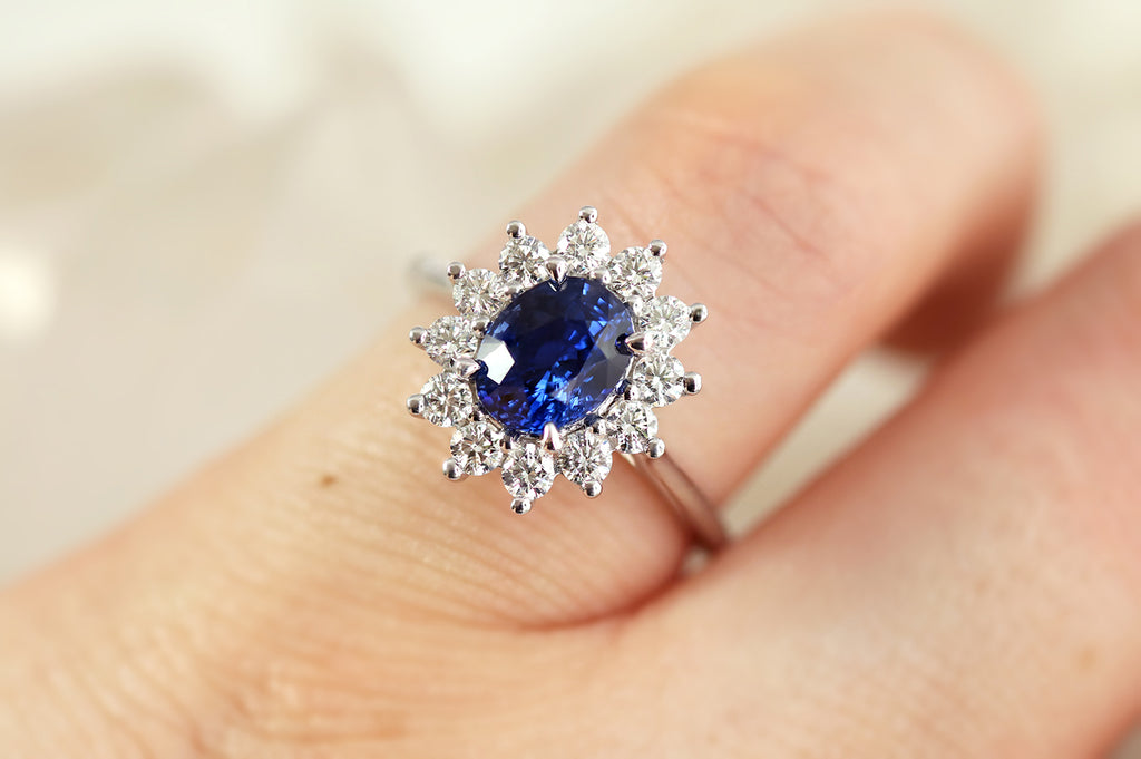 white gold engagement ring featuring oval Ceylon Sapphire and white diamond halo