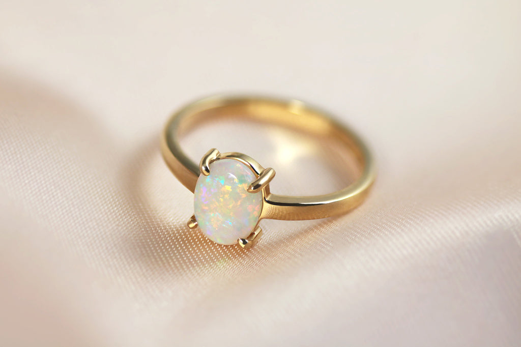 yellow gold ring featuring an oval shaped Lightning Ridge opal in a four claw setting