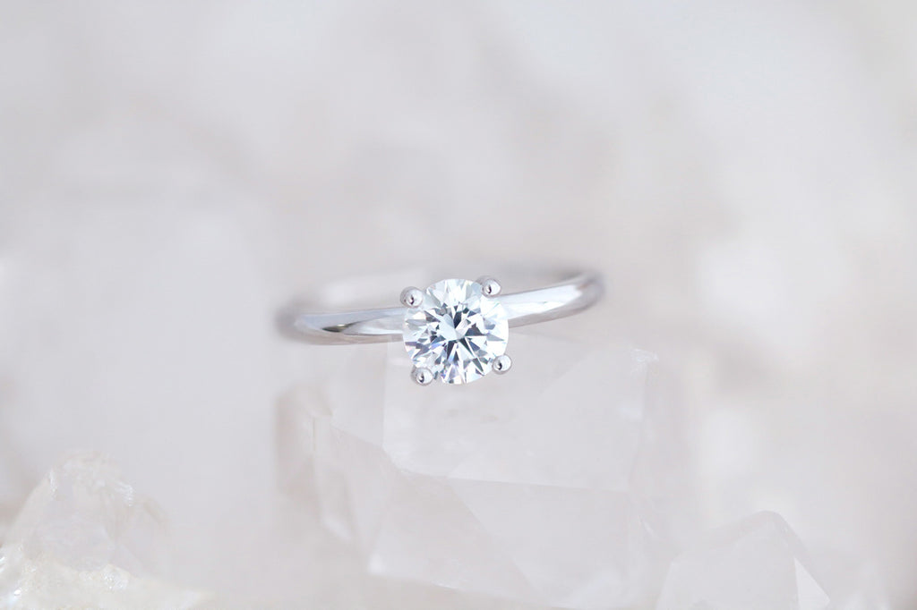 white gold engagement ring featuring round brilliant cut diamond in a four claw setting