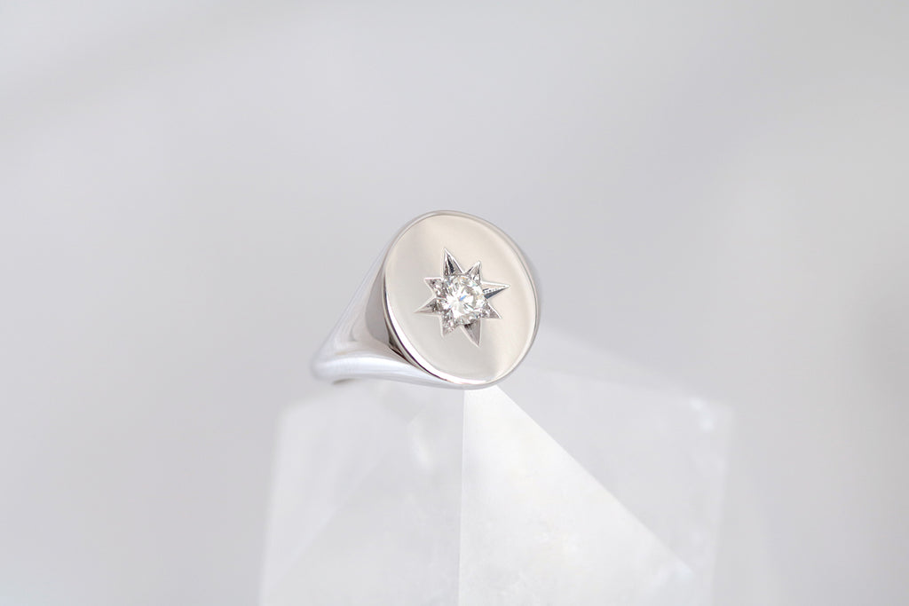 white gold oval shaped signet ring with a round brilliant cut diamond set in the centre