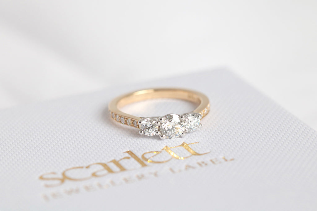 yellow gold engagement ring featuring three round brilliant cut diamonds
