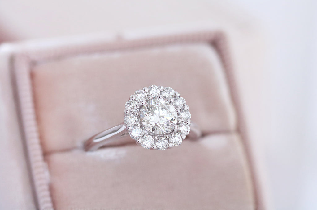 white gold engagement ring featuring round brilliant cut centre diamond and a white diamond halo