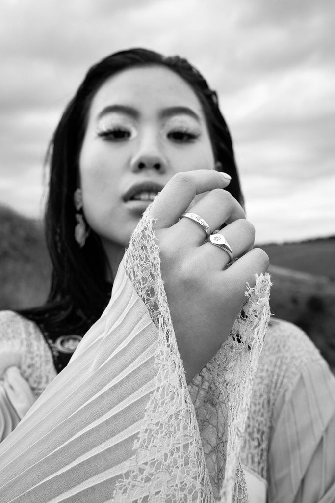 a model holding her hard towards the centre of the frame, she has rings on her fingers