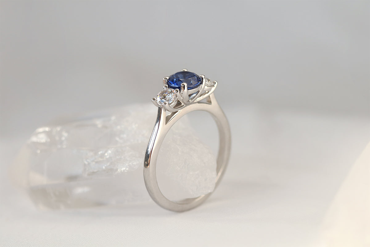 side profile of white gold diamond and sapphire engagement ring