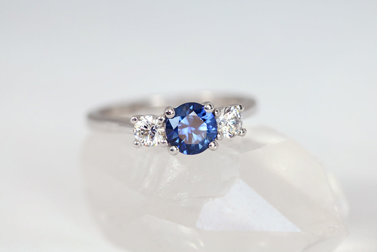 round sapphire and diamond trilogy engagement ring in white gold