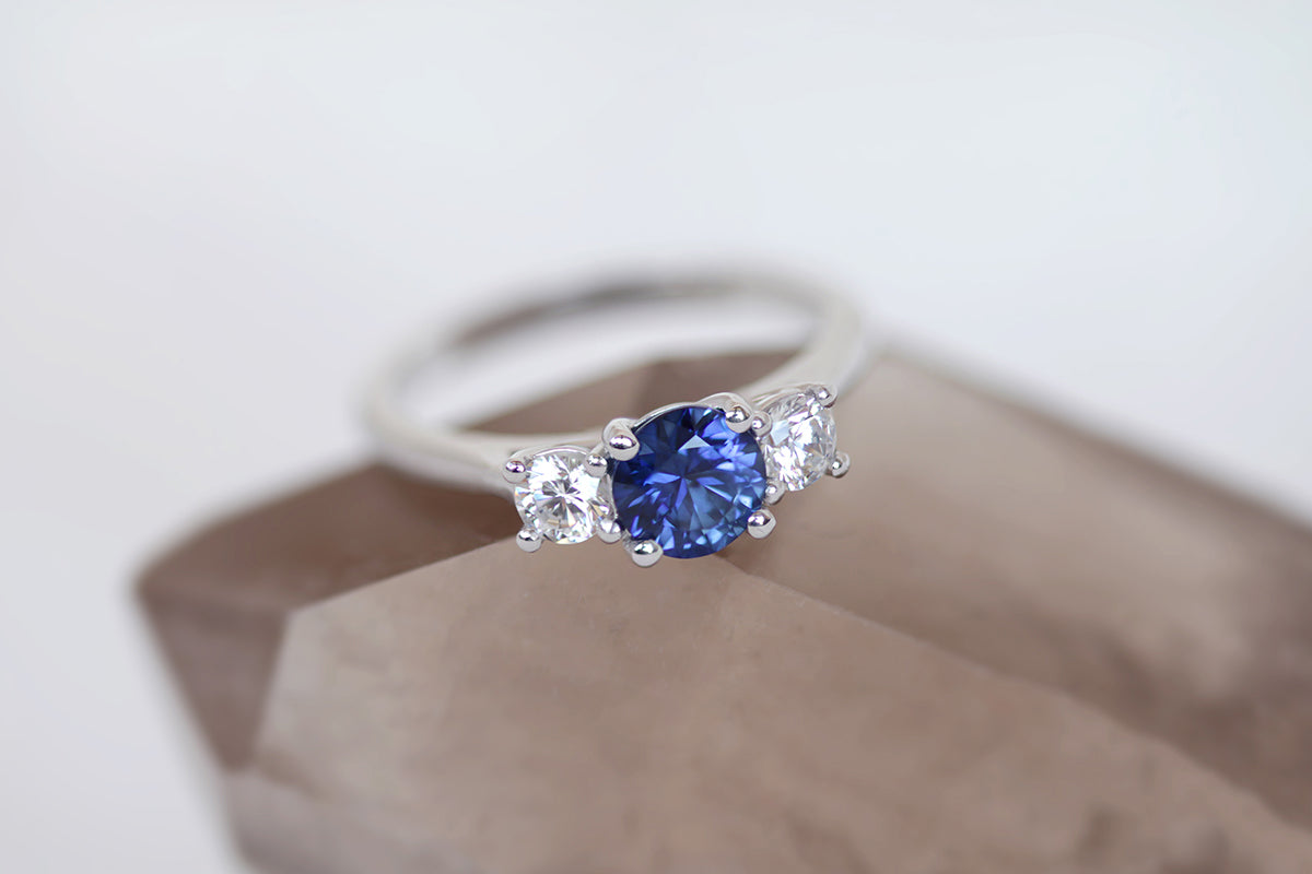 three stone engagement ring with diamonds and sapphire