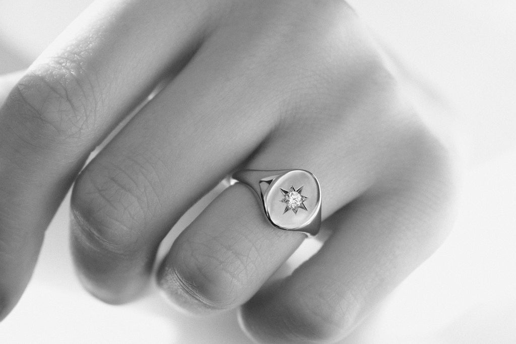 Rose gold signet ring with diamond worn on ring finger