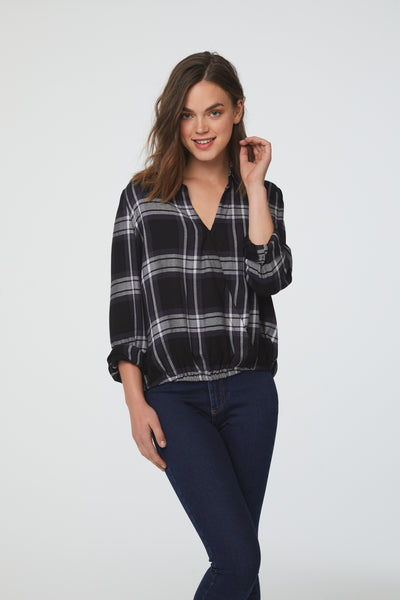 Woman wearing a black and white plaid, Long Sleeve Collared V-Neck Shirt with Wrap Silhouette and Elastic Bottom Hem