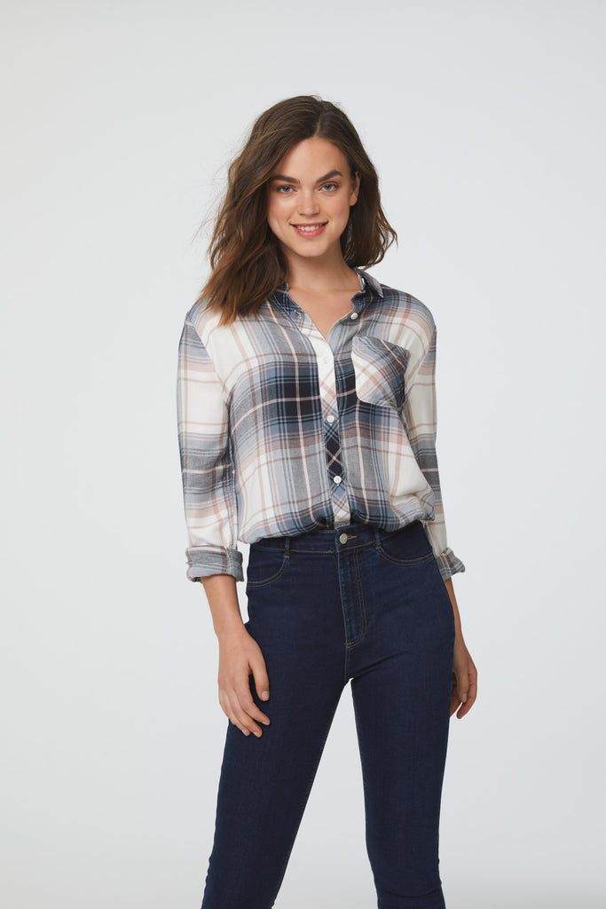 woman wearing a long sleeve, button-down, faded white, blue and black plaid shirt with single chest pocket