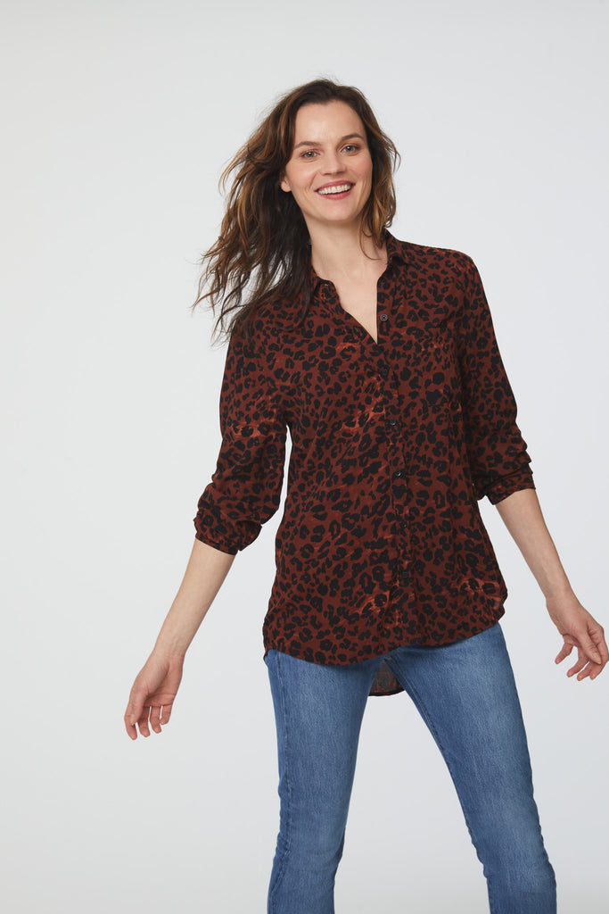 woman wearing a red leopard print, long sleeve, button-down blouse with a single chest pocket and drop back hem