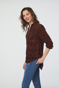 side view of woman wearing a red leopard print, long sleeve, button-down blouse with a single chest pocket and drop back hem