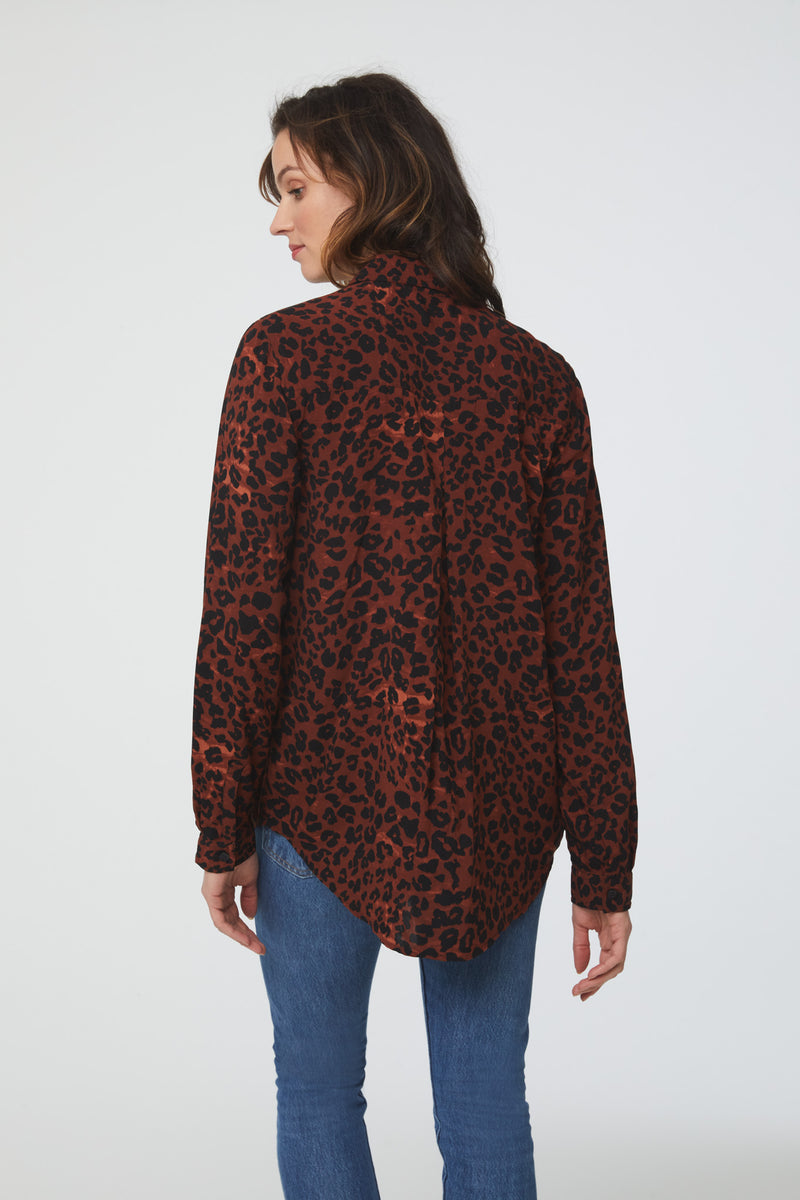 back view of woman wearing a red leopard print, long sleeve, button-down blouse with a single chest pocket and drop back hem