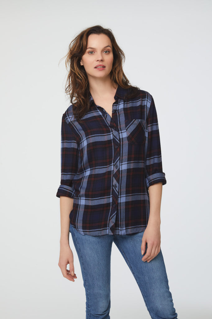 woman wearing a long sleeve, button-down, navy plaid shirt with blue and red accents and single chest pocket
