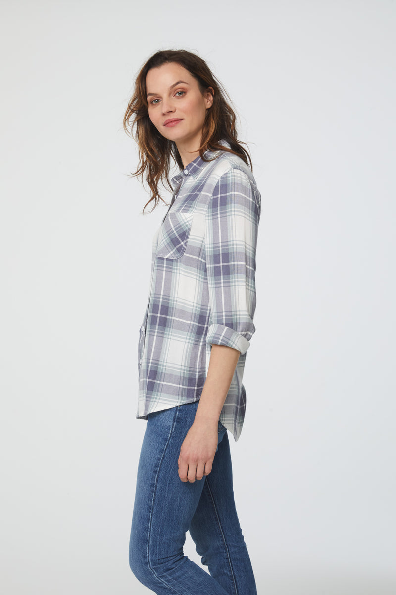 side view of woman wearing a long sleeve, white, green and blue plaid, button-down shirt with single chest pocket