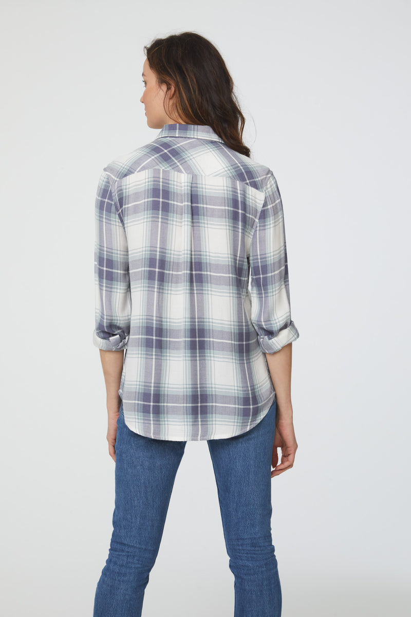 back view of woman wearing a long sleeve, white, green and blue plaid, button-down shirt with single chest pocket