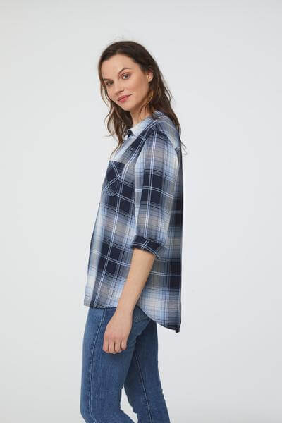 side view of woman wearing a long sleeve, button-down, blue and black plaid shirt with single chest pocket