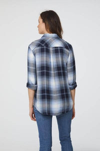 back view of woman wearing a long sleeve, button-down, blue and black plaid shirt with single chest pocket