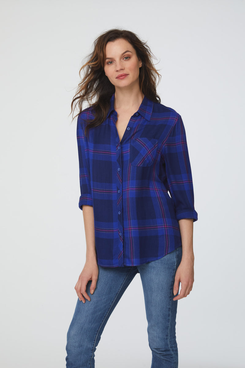 Woman wearing a long sleeve, button-down shirt in an indigo and magenta accent plaid pattern with single chest pocket and rolled cuff sleeves