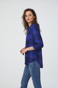 Side view of a woman wearing a cuffed long sleeve, button-down shirt in an indigo and magenta accent plaid pattern with single chest pocket and drop back hem