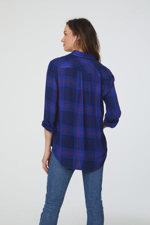 back of a woman wearing a cuffed long sleeve, button-down shirt in an indigo and magenta accent plaid pattern