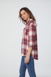 Side view of side view of woman wearing a long sleeve, button-down, dusty crimson red plaid shirt with single chest pocket