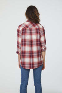 back of side view of woman wearing a long sleeve, button-down, dusty crimson red plaid shirt with single chest pocket