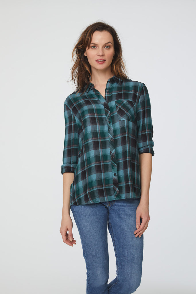 woman wearing a long sleeve, button-down, green-blue plaid shirt with single chest pocket