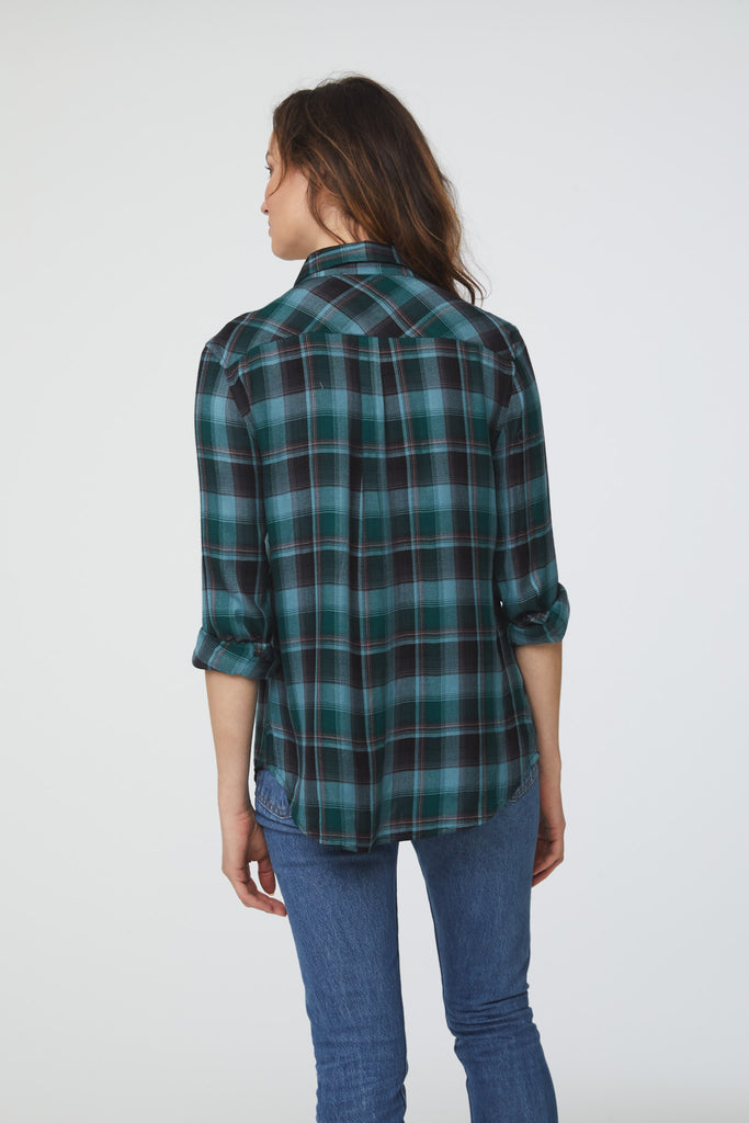 Back view of woman wearing a long sleeve, button-down, green-blue plaid shirt with single chest pocket