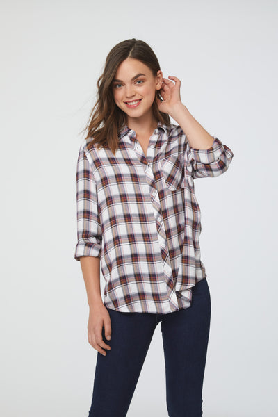 Woman wearing a long sleeve, button-down plaid shirt in white and copper with a single chest pocket