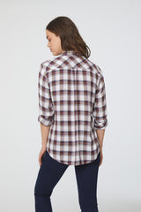 Back view of woman wearing a long sleeve, button-down plaid shirt in white and copper with drop back hem