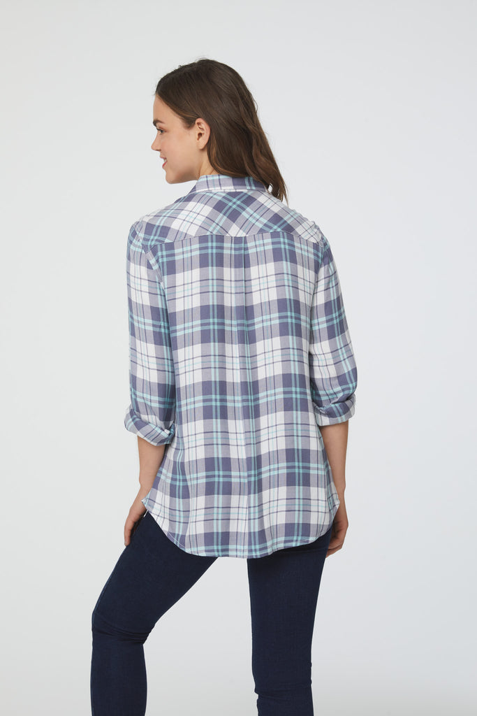 back view of woman wearing a long sleeve, white, purple and blue plaid, button-down shirt with single chest pocket