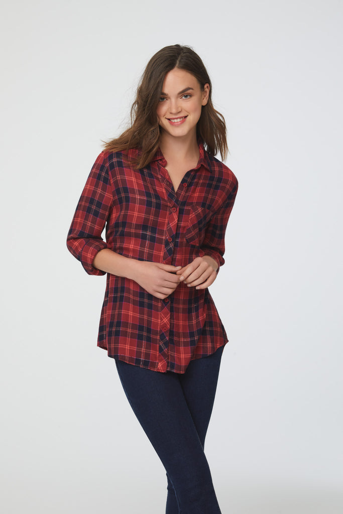 woman wearing a long sleeve, button-down, red-orange plaid shirt with single chest pocket