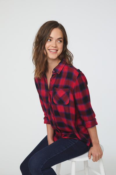 Woman wearing a cuffed long sleeve, button-down plaid shirt in red and black with a single chest pocket