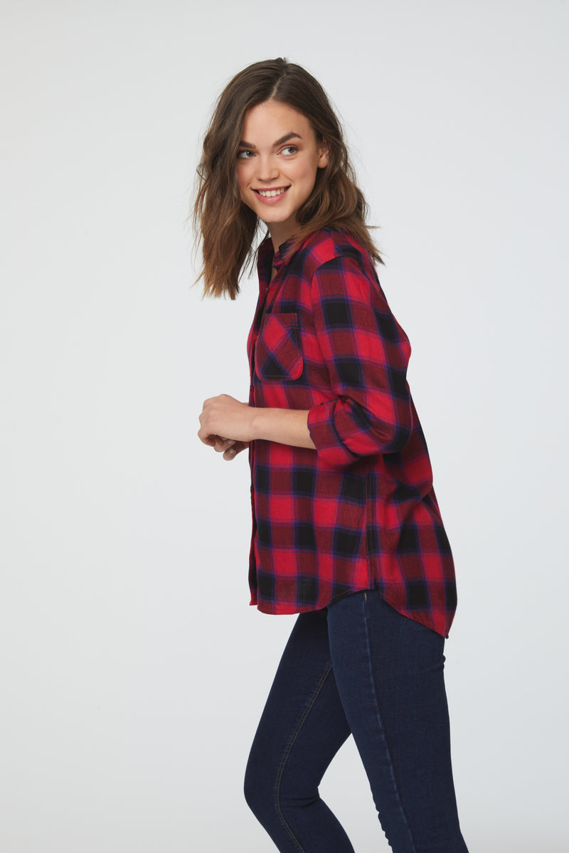 Side view of a woman wearing a cuffed long sleeve, button-down plaid shirt in red and black with a single chest pocket