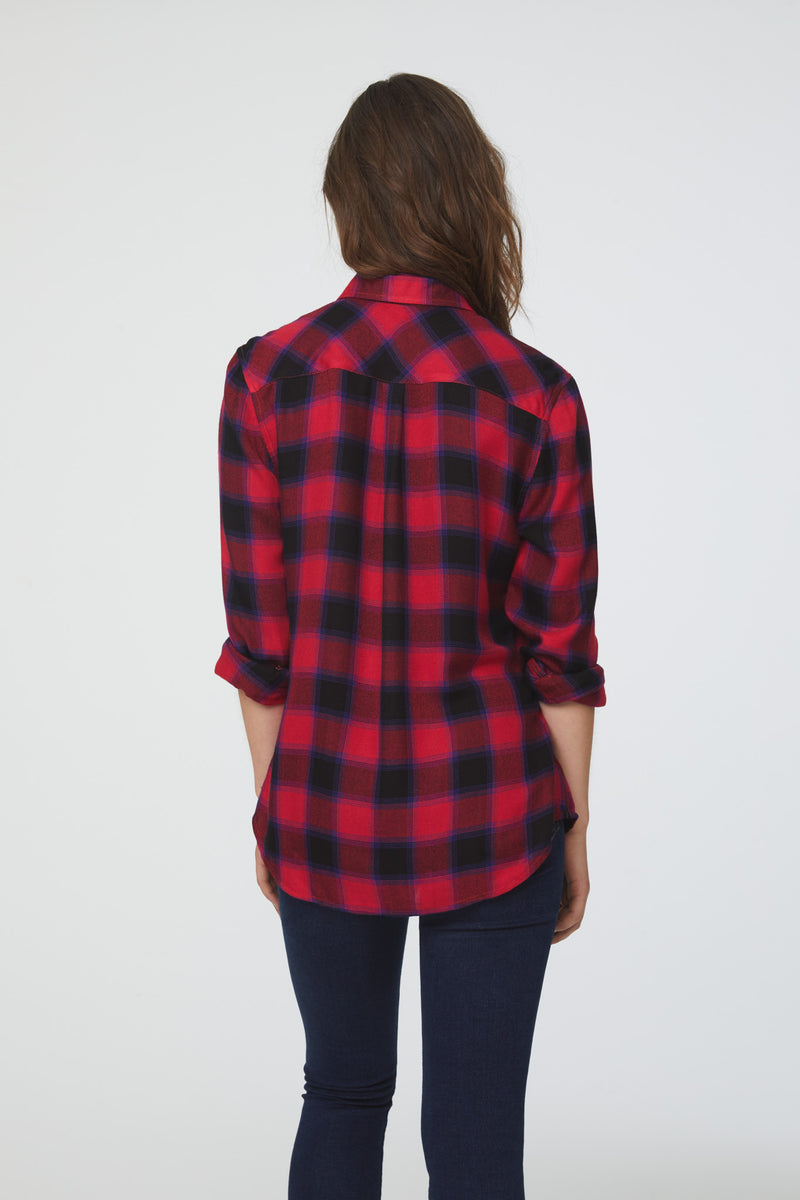 Back of a woman wearing a cuffed long sleeve, button-down plaid shirt in red and black with a drop back hem