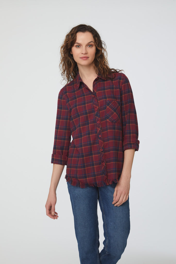 Woman wearing long sleeve, button front flannel shirt in red and blue plaid with frayed hem detailing