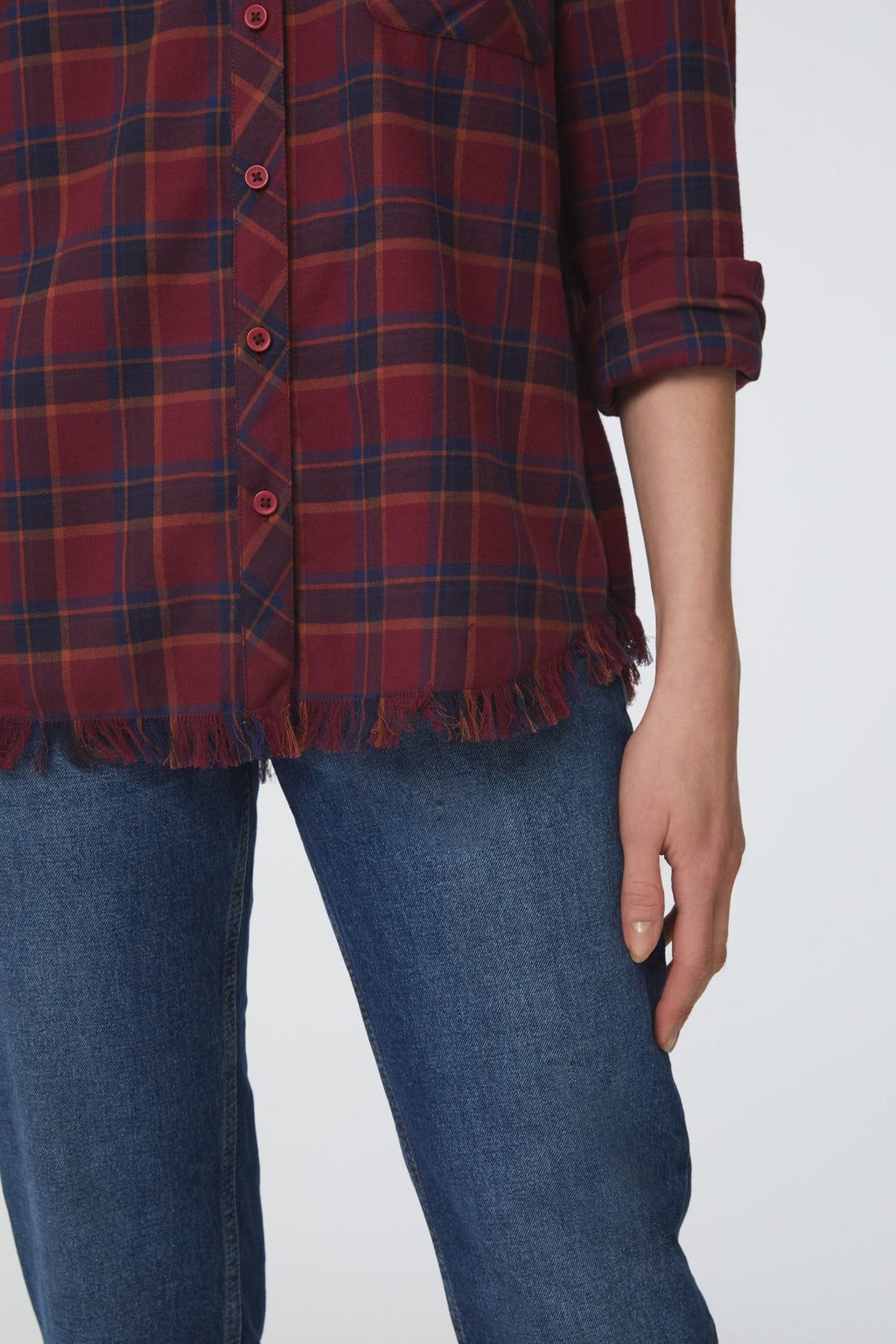 detail of frayed hem on red and blue plaid shirt