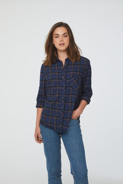 Woman wearing long sleeve, button front flannel shirt in blue, black, and yellow plaid with frayed hem detailing