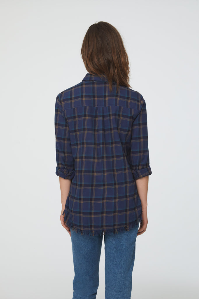 back view of Woman wearing long sleeve, button front flannel shirt in blue, black, and yellow plaid with frayed hem detailing