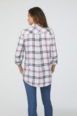 back view of woman wearing a long sleeve, white, purple and black plaid, button-down shirt with single chest pocket