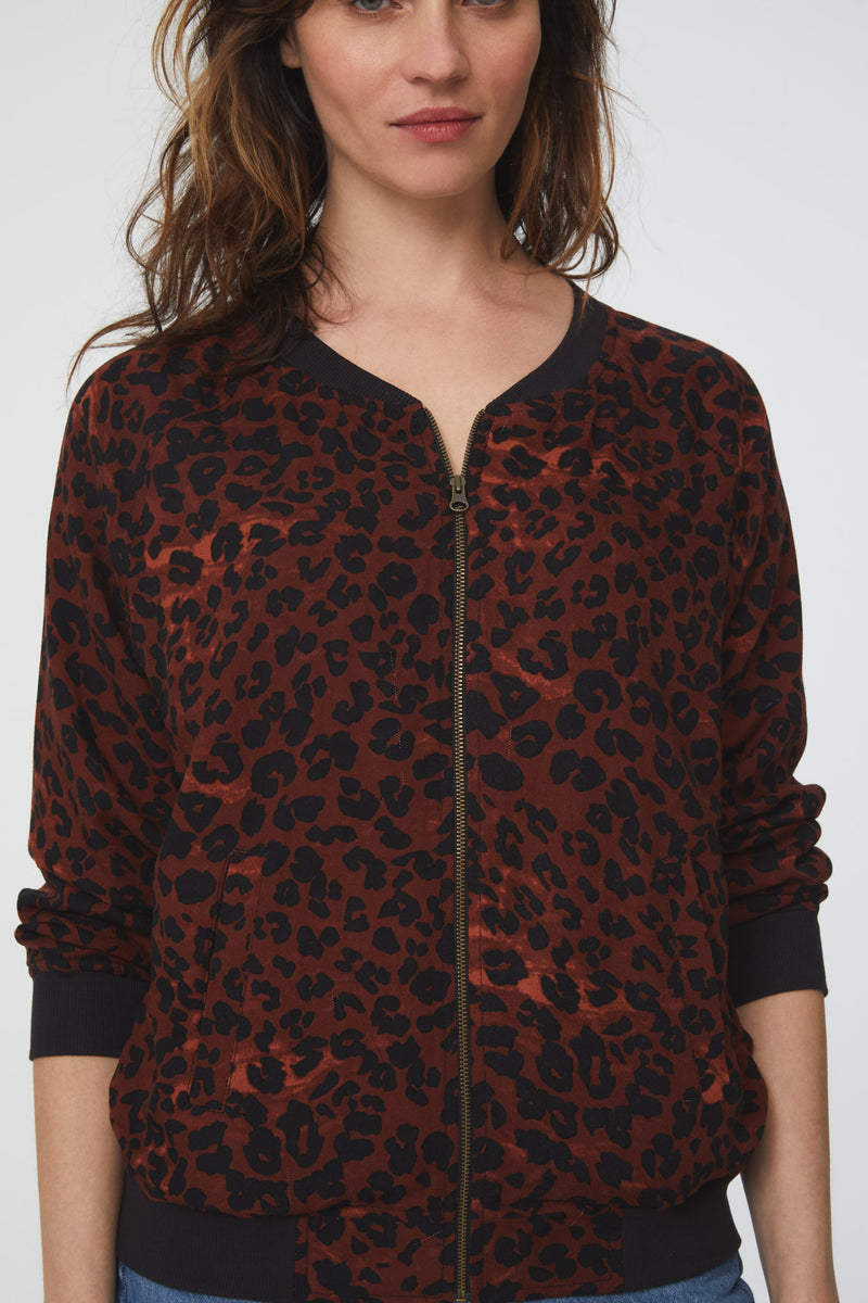 Close view of faded red and black leopard print, lightweight bomber jacket