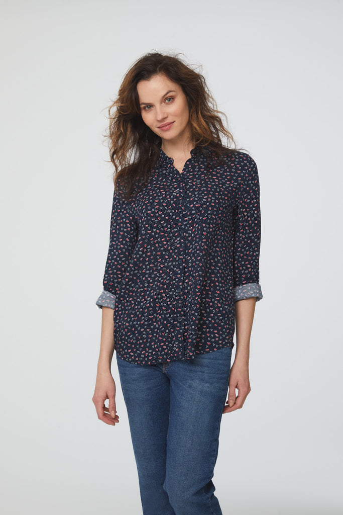 woman wearing a navy, long sleeve, button-down blouse in lips-and-hearts print with single chest pocket and drop back hem