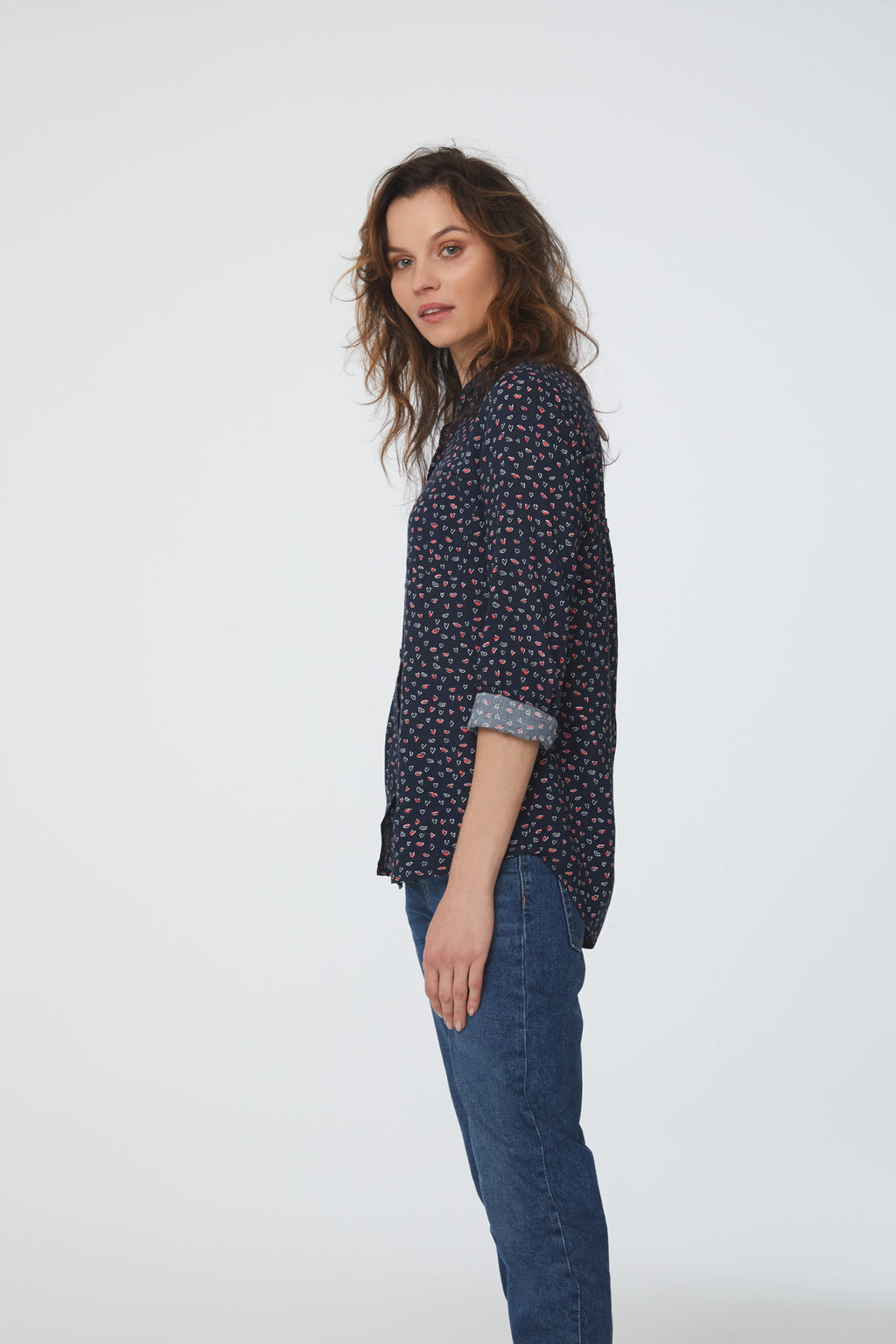 side view of woman wearing a navy, long sleeve, button-down blouse in lips-and-hearts print with single chest pocket and drop back hem