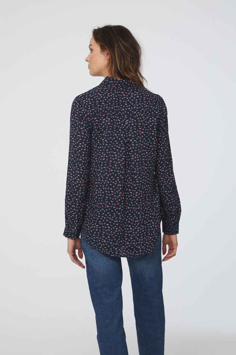 back view of woman wearing a navy, long sleeve, button-down blouse in lips-and-hearts print with single chest pocket and drop back hem