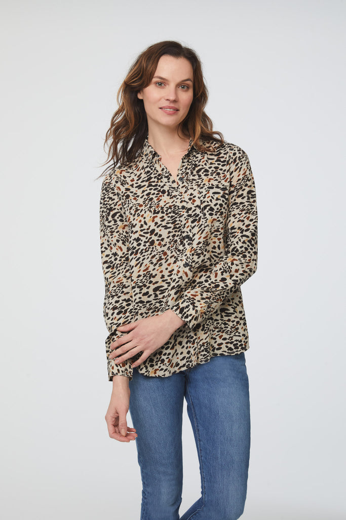 woman wearing a light animal print, long sleeve, button-down blouse with a single chest pocket and drop back hem